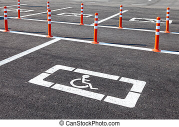 White wheelchair icon on a gray asphalt parking lot