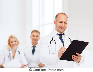 smiling male doctor with clipboard and stethoscope -...