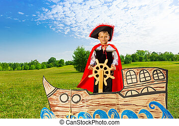 Boy as pirate stands on ship and holds the helm - Boy...