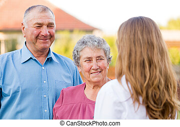 Elderly care - Happy elderly couple talking with their carer