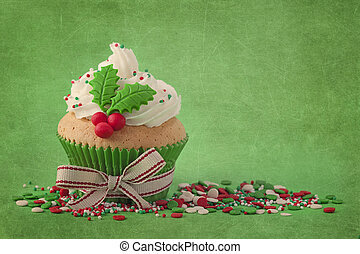 Christmas cup cakes with holly berry on a green background