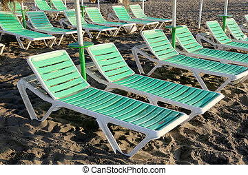 Beach lounge chair at lonely sandy beach. Costa del Sol (Coast of the Sun), Malaga in Andalusia, Spain