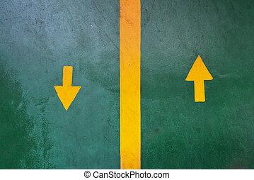 Two yellow arrows forward backward on green asphalt...