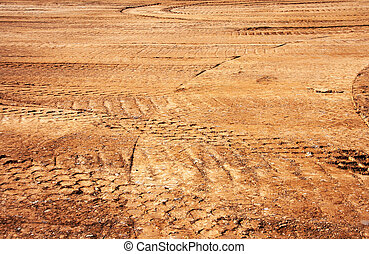 wheel's trail tread in the red mud as a background -...
