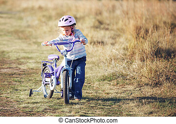 Small funny kid riding bike with training wheels