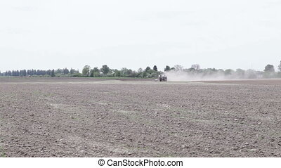 Tractor plowing the black earth plow field on a sunny day