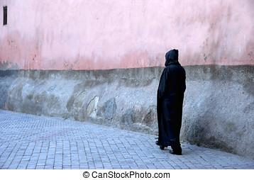 Man in djelleba walking in a street in Marrakesh,Morocco