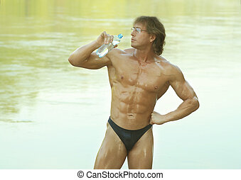 Naked muscular man drinks water from a bottle