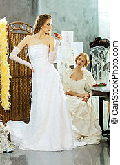 Girl tries on a wedding dress in the clothing design studio