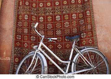 White bike in front of a shop that sells traditional carpets...