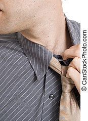 Man pulling shirt collar and tie