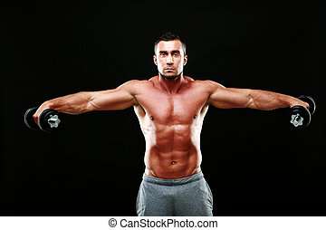 Portrait of a muscular man lifting dumbbells over black...