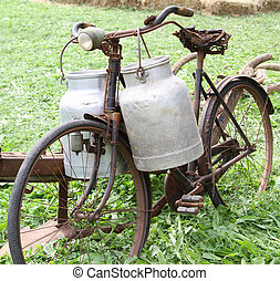 rusty old bike of the milkman with two old milk cans and...