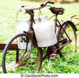 very rusty old bike of the milkman with two old milk cans...