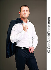 Handsome businessman holding his jacket over shoulder on...