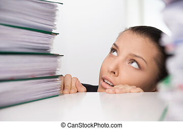 Business woman sitting under table and looking on folders....