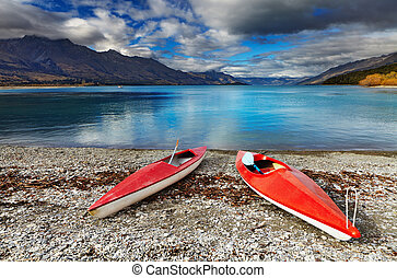 Wakatipu Lake, New Zealand - Red kayaks at the lakeside,...