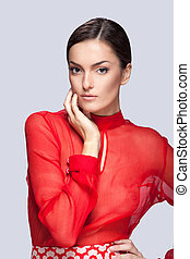 portrait of beautiful woman with clean face skin. Glamorous young woman in red on grey background and hand touching face
