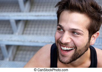 Happy young man with beard laughing - Close up portrait of a...