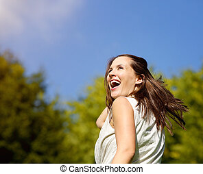 Carefree woman laughing outdoors - Close up portrait of a...