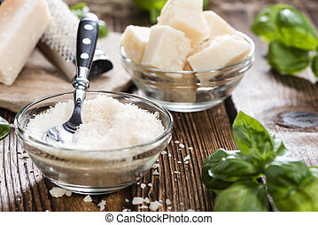 Heap of grated Parmesan (close-up shot) on wooden background