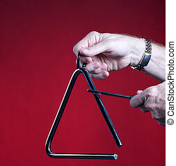 Triangle Played Isolated on Red - A musical triangle being...