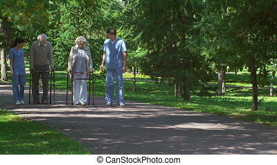Patients with Walkers Accompanied b - Two young caregivers...