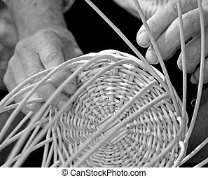 hands of craftsman create a wicker basket - hands of...