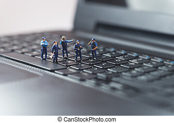 Miniature police squad protecting laptop computer....