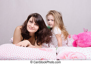 Mom and daughter with a hairbrush in her bed - Daughter...