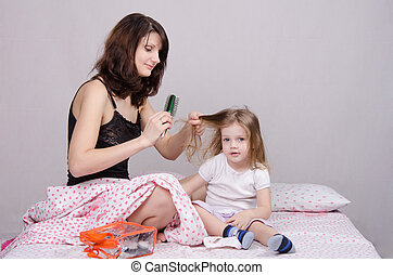 Mom combing her daughter in the morning - Mom and daughter...