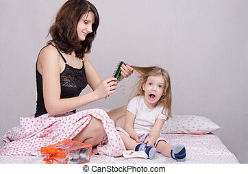 Mom combing hair-year old daughter - Mom and daughter with...