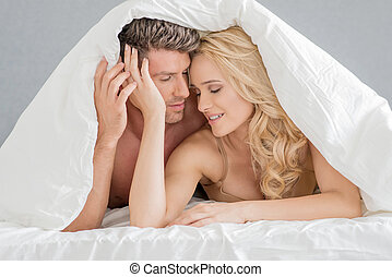 Sweet Young Couple on Bed Fashion Shoot with White Cover