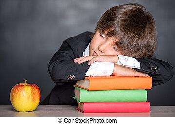 Sleeping school boy in classroom