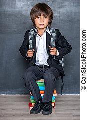 School boy sitting on books