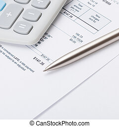 Calculator and pen over some receipt - 1 to 1 ratio