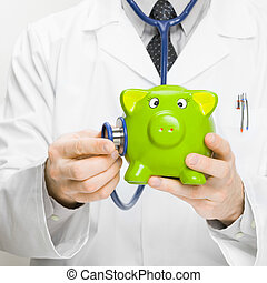 Medical doctor holding stethoscope and piggybank in hand - 1...