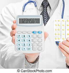 Medical doctor holdling calculator and pills in his hands -...