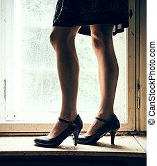 Woman legs in front of a window