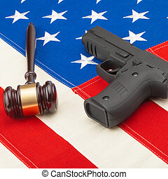Wooden judge gavel and gun over big USA flag - 1 to 1 ratio