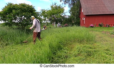 Man cut high grass - Man with trimmer cut high grass in...