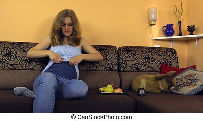 pregnant woman fix pants - Pregnant woman lie on couch and...