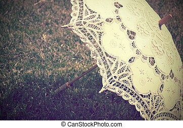 lacy parasol on the grass close up tinted vintage,...