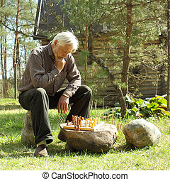 gray-haired man playing chess