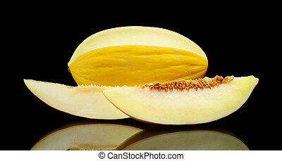 Studio shot of sliced Canary melon isolated black - Studio...