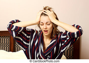 woman in a bathrobe suffering from a headache