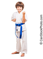 I can defence myself Full length of little boy in karate...