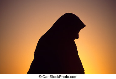 Arab woman with veil in backlight