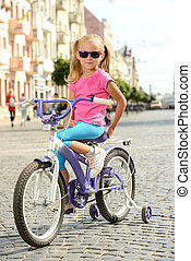 Street bike - Beautiful smiling little girl riding a bike on...