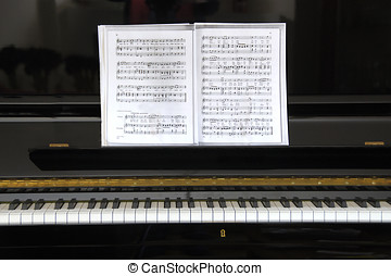 Black piano with old sheet music